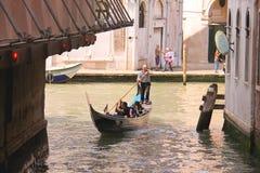 Gondoliere segelt mit den Touristen, die in einer Gondel hinunter die Erzählung sitzen Lizenzfreie Stockfotos
