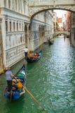 Gondoliers flottant sur un canal grand à Venise Photographie stock