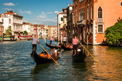 Gondoliers flottant sur un canal grand, Venise Photo stock