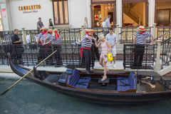 Gondoliers helping tourist to board the gondola ride at Grand Canal at The Venetian Resort Royalty Free Stock Image