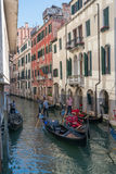 Gondoliers navigate gondolas through a canal in Venice, Italy. Stock Photos