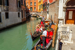 Gondoliers with rourists at canal in Venice Stock Images