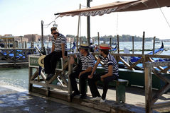 Gondoliers in Venice - Italy. Gondoliers with the typical headgear on a Grand Canal of Venice in Italy Stock Image