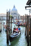 Gondoliers in Venice. Water channel with gondolas with gondoliers and tourists in Venice (Italy) with Church of the Santissimo Redentore behind Stock Photography