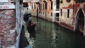 Gondoliers are walking through narrow channels. Venice Italy stock video footage