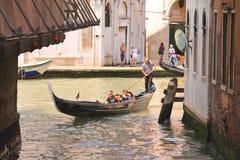 Gondoljären seglar med turister som sitter i en gondol, Venedig, Ital Arkivfoto