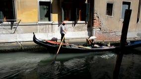 Gondoljären transporterar turister i en gondol på en smal kanal stock video