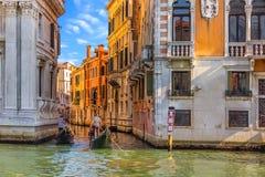 Gondoljärer på arbete i en typisk kanal av Venedig royaltyfri bild