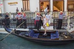 Gondoljärer som hjälper turisten att stiga ombord gondolritten på Grand Canal på den Venetian semesterorten Royaltyfri Bild