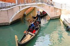 Gondoljärsegling med turister i en gondol längs en av caen Royaltyfria Foton