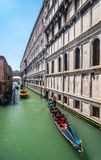 Gondoljär med turister i gondol på kanalen Rio di Palazzo Royaltyfri Bild