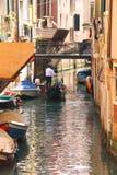 Gondoljären seglar med turister som sitter i en gondol ner berättelsen Arkivfoto