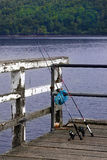 Gone fishin'. Two fishing rods on jetty over a Scotish loch Stock Image