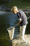 Gone fishing. Boy fishing in pond with net Stock Photography