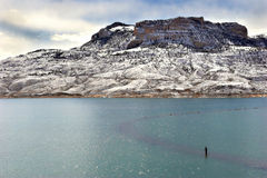 Gone fishing. A lonesome fisherman on bufallo bill reservoir, just outside of cody, wyoming stock photo