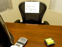 Gone Fishing!. Empty desk with a gone fishing sign Royalty Free Stock Image