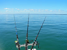 Gone Fishing. Three fishing rods cast into a blue calm sea Stock Photos