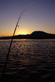 Gone Fishing. Silhouette of a fishing rod and mountains over ripply water. This photo was taken in Zambia in the Zambezi river stock photo
