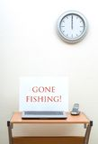 Gone Fishing. Office desk with gone fishing sign on open laptop next to portable phone, clock on wall royalty free stock image