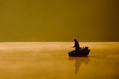 Gone Fishing. A single angler enjoys fishing from a boat on a beautiful morning Royalty Free Stock Images