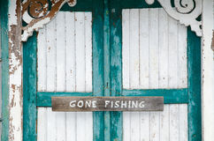 Gone fishing sign at weathered doors. Closeup of a gone fishing sign on a weathered door with cracked painting in white and green royalty free stock photos