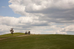 Gone Golfing. Golf cart on path with blue skies and white clouds in background Stock Photo