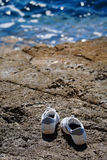Gone swimming. Lonely sports shoes at the seaside Royalty Free Stock Photos