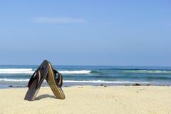 Beach flip-flops next to water edge Royalty Free Stock Photo