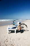 Gone swimming. Bike leaning against beach chair Royalty Free Stock Photo