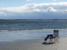 Gone swimming. Gone swimming; a couple away into the water at Carlingford Lough, Northern Ireland, leaving shoes and towels at the folding chair on the beach Stock Image