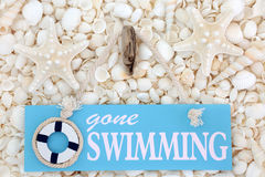 Gone Swimming Sign on Seashells Stock Photo