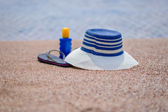 Gone swimming. A sunhat, sunscreen and pair of slip slops are left on a sandy tropical beach overlooking the sea as the owner goes off to enjoy a swim Royalty Free Stock Photo