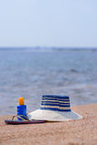 Gone swimming. A sunhat, sunscreen and pair of slip slops are left on a sandy tropical beach overlooking the sea as the owner goes off to enjoy a swim Royalty Free Stock Image