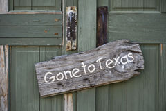 Gone to Texas sign on door. Closeup of wooden gone to Texas sign on closed door Royalty Free Stock Images