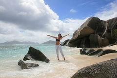 Gone with the wind. Beautiful women on the beach of Anse Source d'Argent, Seychelles Island, with amazing rocks on the background and beautiful clouds and Stock Images