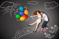 Gone with the wind. Happy valentines love story concept of a romantic couple holding balloons blowing with the wind against chalk drawings background Stock Photography