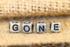 Gone word cube beads on sockcloth Royalty Free Stock Image