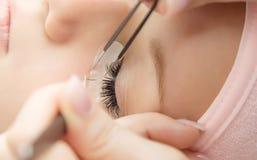 Ögonfransförlängningstillvägagångssätt Kvinnan synar med långa ögonfranser Arkivbild