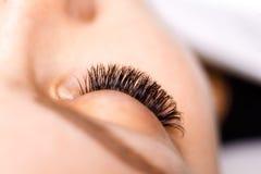 Ögonfransförlängningstillvägagångssätt Kvinnan synar med långa ögonfranser Snärtar slut upp, makro, selektiv fokus Arkivbilder