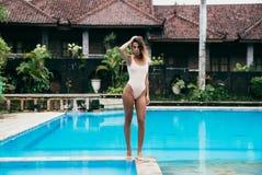 Gongerous-Mädchen im Bikini gehend nahe Pool mit blauem Wasser Sexy Modell mit einer Sportzahl steht still Junge Frau mit Lizenzfreie Stockbilder