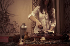 Gongfu tea ceremony. A young girl holds a Chinese tea ceremony royalty free stock photography