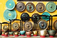Gongs and singing bowls - traditional Asian musical instruments on a street market. Hoi An, Vietnam royalty free stock photography