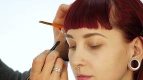 ?gonmakeupkvinna som applicerar ?gonskuggapulver Stylisten g?r sminket f?r kvinnlig vid eyeliner
