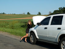 Gonna be late. Blonde girl in business suit under hood of broken down vehicle on the side of the road stock photos