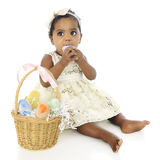 Gonna' Eat My Easter Egg!. An adorable, dressed up baby girl prepared to eat a whole egg from her Easter basket which sits by her side.  On a white background Royalty Free Stock Photo