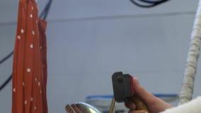 Gonna rivestente di ferro della mano della lavoratrice nel lavaggio a secco video d archivio