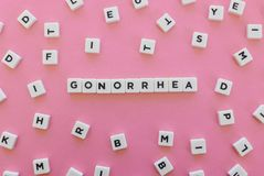 Gonorrhea word made of square letter word on pink background. royalty free stock photos