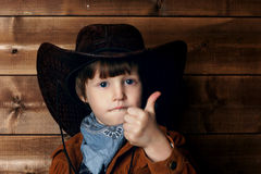 That is good!. Studio portrait of little boy in cowboy costume in wild west style interior showing thumbs up Stock Image