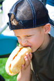 So good!. A boy eating a hot dog outfoors Royalty Free Stock Photos