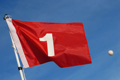 Good Aim. A red golf flag with the number 1 against a blue sky background with a golf ball flying past the flag Stock Photography